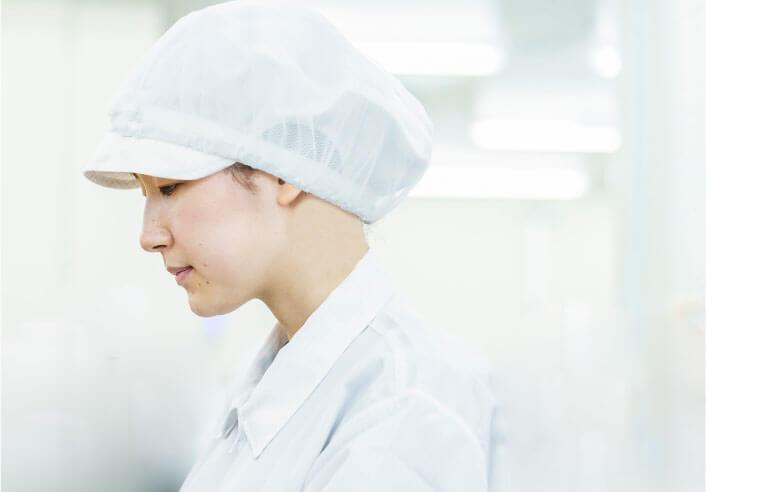 クリーンスーツを着た女性スタッフの横顔