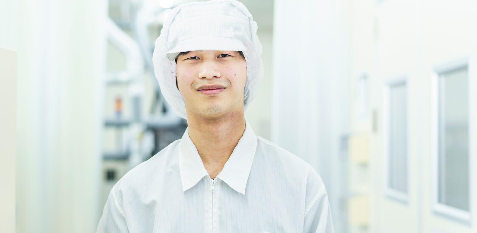 クリーンスーツを着た男性スタッフの正面写真