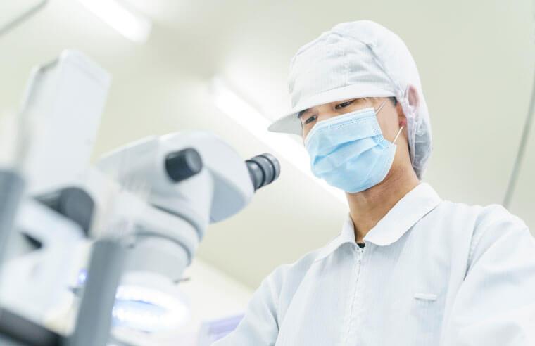 顕微鏡を覗く男性スタッフを下から写した写真